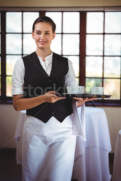 Portrait of smiling waitress holding a tray of coffee cups Stock photo © wavebreak_media