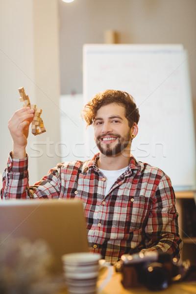 Happy graphic designer holding a wooden block Stock photo © wavebreak_media
