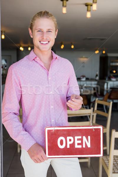 Restaurant manager holding open signboard Stock photo © wavebreak_media