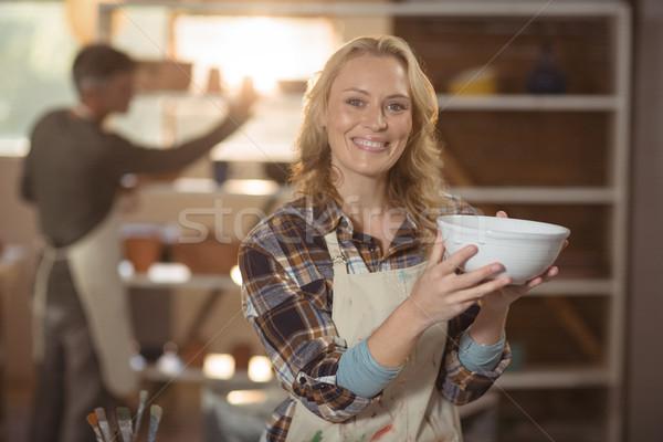 Smiling female potter checking bowl in pottery workshop Stock photo © wavebreak_media