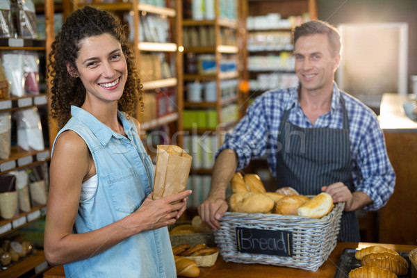 Portrait of smiling woman purchasing bread at bakery store Stock photo © wavebreak_media