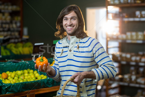 Man with a basket selecting bell pepper in organic section Stock photo © wavebreak_media