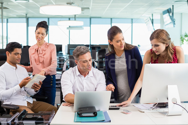 Business colleagues interacting with each other at desk in office Stock photo © wavebreak_media