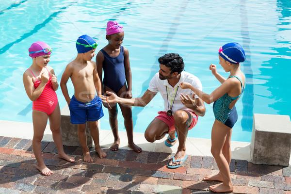 Male trainer assisting children at poolside Stock photo © wavebreak_media