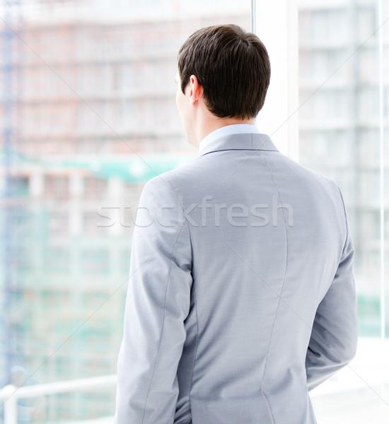 Thinking businessman looking through a window  Stock photo © wavebreak_media