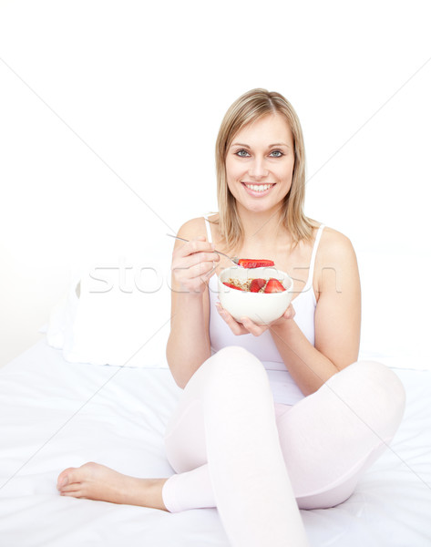 Delighted woman eating cereals with strawberries Stock photo © wavebreak_media