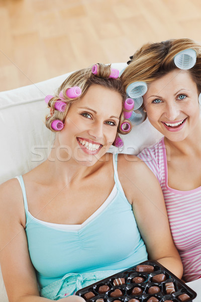 Delighted women wearing hair rollers eating chocolate looking at the camera in the living-room Stock photo © wavebreak_media