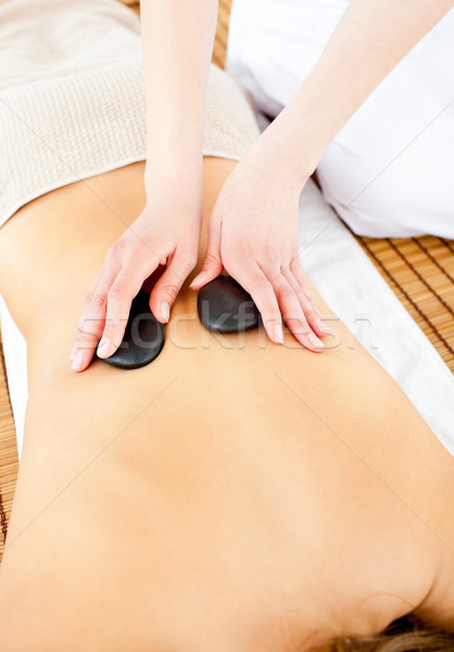 Close-up of a young woman receiving a back massage with hot stone in a health spa Stock photo © wavebreak_media