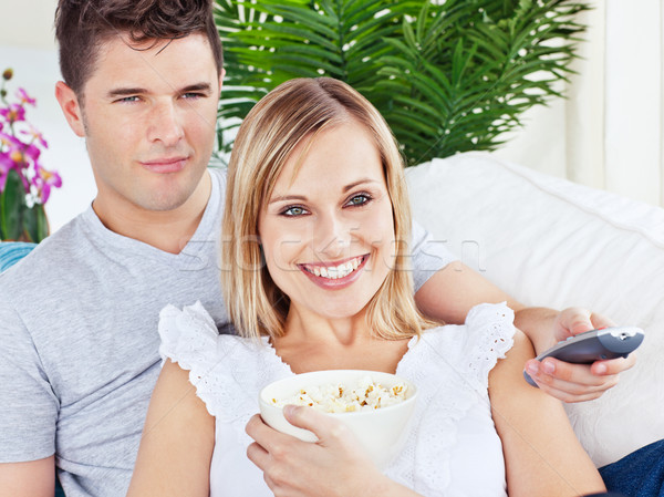 Portrait of an attractive couple with pop-corn and remote relaxing on the sofa at home Stock photo © wavebreak_media