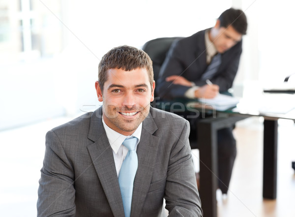 Happy businessman in the foreground during a meeting with a colleague at the office Stock photo © wavebreak_media