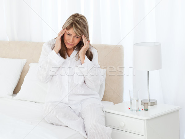 Stock photo: Woman having a headache on her bed