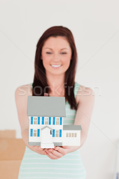 Pretty red-haired woman holding a miniature house while standing on the floor at home Stock photo © wavebreak_media