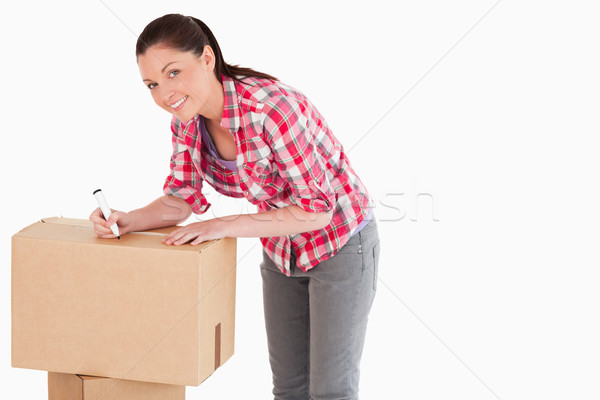 Beautiful woman writing on cardboard boxes with a marker while standing against a white background Stock photo © wavebreak_media