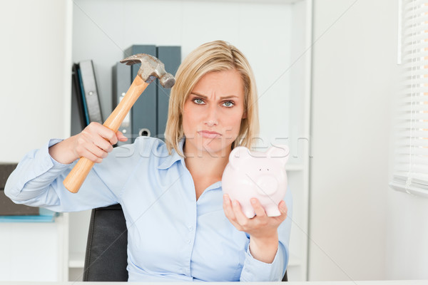 sulking woman wanting to destroy her piggy bank in her office Stock photo © wavebreak_media