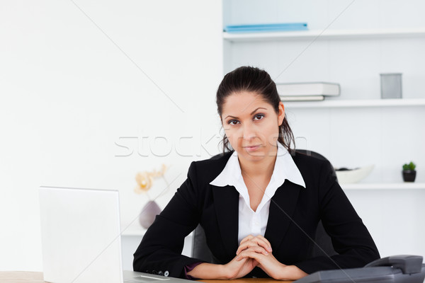 A serious businesswoman is sitting at her workplace Stock photo © wavebreak_media