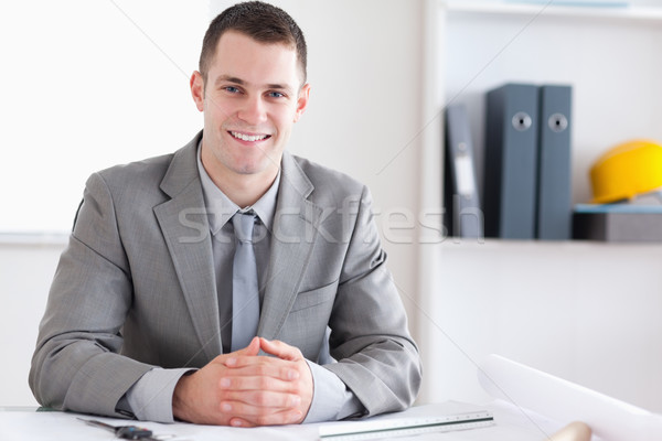 Smiling architect with folded hands sitting behind a table Stock photo © wavebreak_media