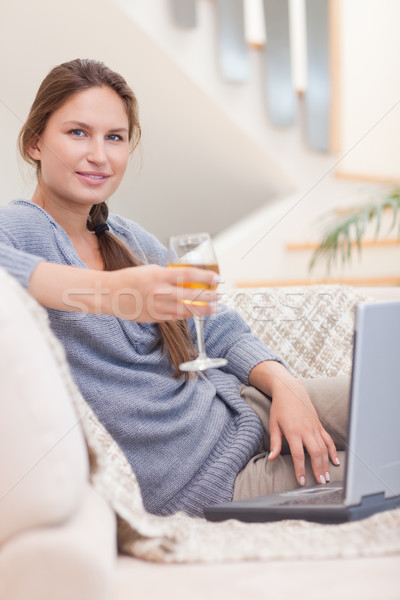 Stock photo: Portrait of a woman having a glass of wine while using her laptop in her living room
