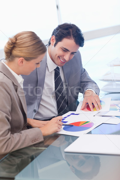 Portrait of smiling business people studying statistics in a meeting room Stock photo © wavebreak_media