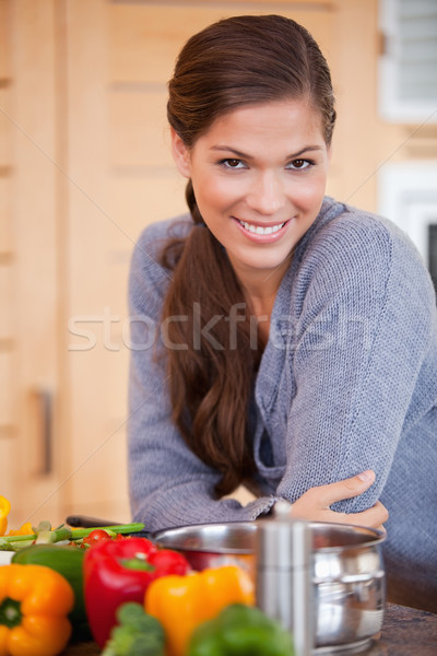 Smiling young woman leaning against the kitchen counter Stock photo © wavebreak_media