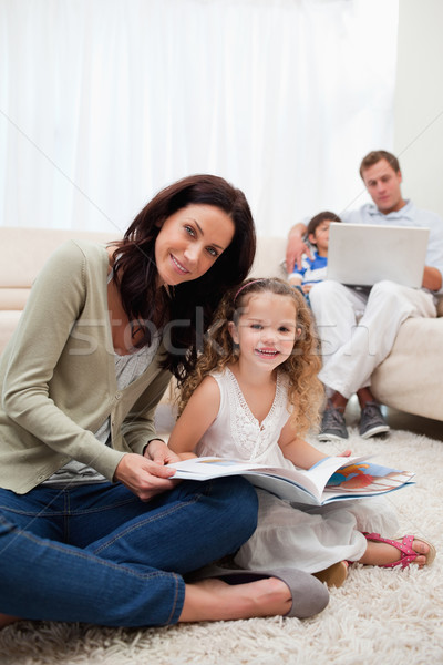 Mother and daughter reading book in together in the living room Stock photo © wavebreak_media