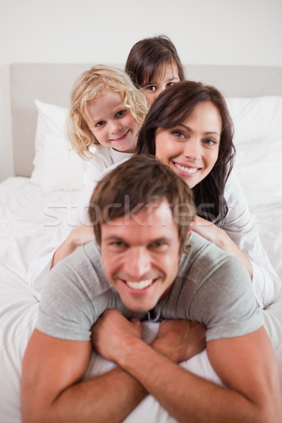 Portrait of a family lying on each other in a bedroom Stock photo © wavebreak_media