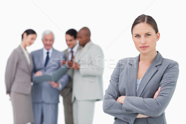 Serious saleswoman with folded arms and team behind her against a white background Stock photo © wavebreak_media