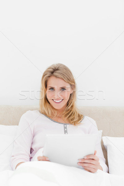 A centered shot of a woman with a tablet pc, looking forward and smiling while in bed. Stock photo © wavebreak_media