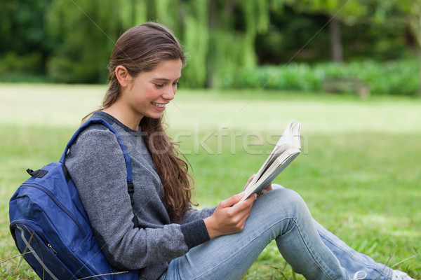Young calm girl sitting on the grass while attentively reading a book Stock photo © wavebreak_media