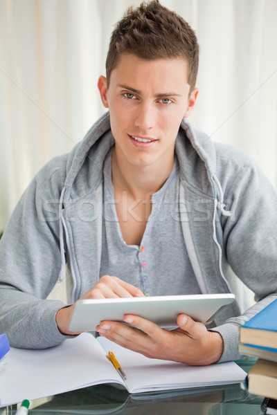 Handsome student using a touch pad while doing his homework Stock photo © wavebreak_media