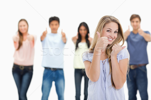 Close-up of people smiling and approving with one young woman in foreground against white background Stock photo © wavebreak_media