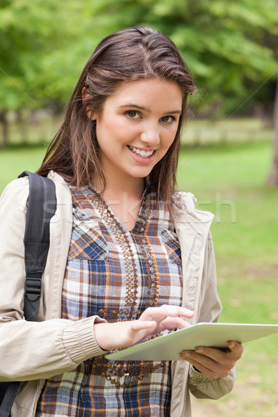 Stock photo: Portrait of a first-year student using a touch pad in a park