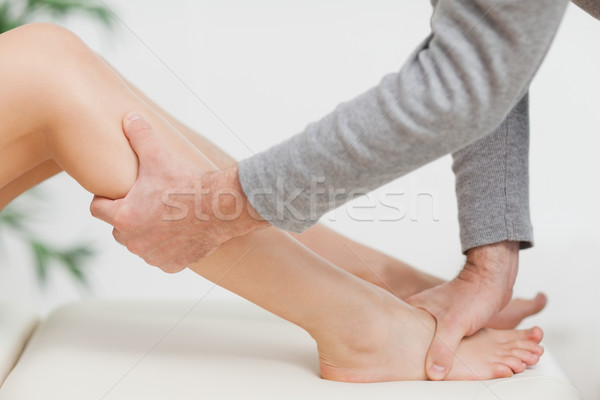 Doctor holding the calf of a patient in a medical room Stock photo © wavebreak_media