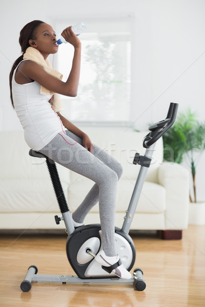 Side view of a black woman on an exercise bike in a living room Stock photo © wavebreak_media