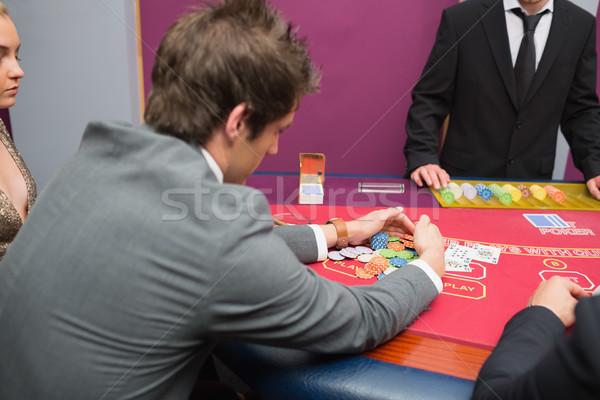 Stock photo: Man taking the pot in poker game at casino