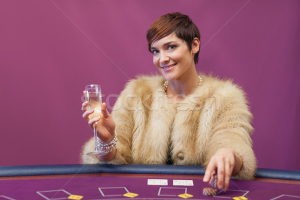 Woman with champagne at poker table in casino Stock photo © wavebreak_media