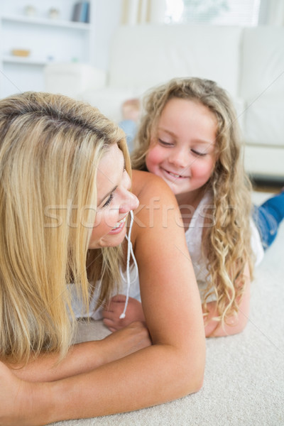 Smiling daughter tickling her mother on living room floor Stock photo © wavebreak_media