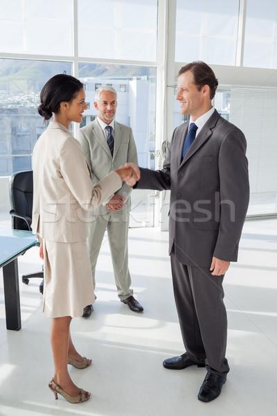 Duas pessoas aperto de mãos colega assistindo feliz aperto de mão Foto stock © wavebreak_media