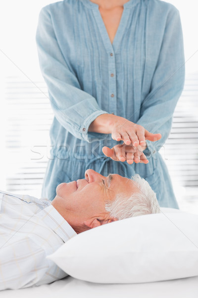 Therapist performing Reiki over forehead of man Stock photo © wavebreak_media