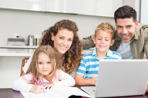 Happy parents colouring and using laptop with their children Stock photo © wavebreak_media