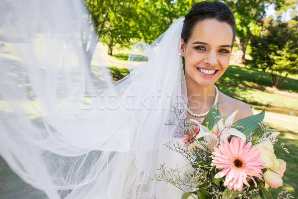 Smiling young beautiful bride with bouquet in park Stock photo © wavebreak_media