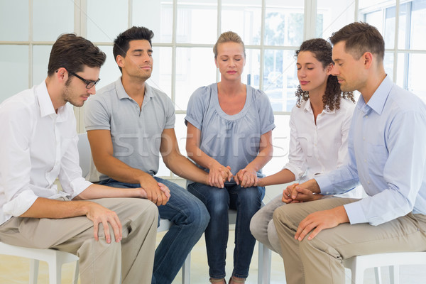 Group therapy in session sitting in a circle holding hands Stock photo © wavebreak_media