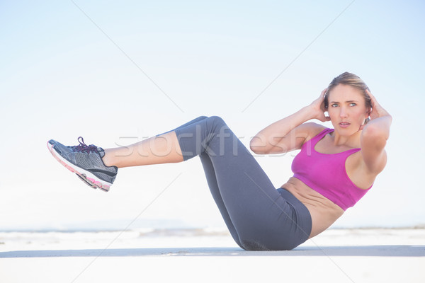 Fit blonde sitting in boat position on the beach Stock photo © wavebreak_media