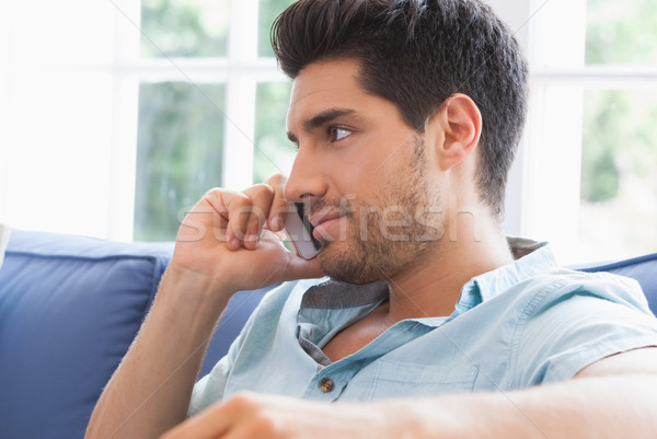 Attractive man making a call on the couch Stock photo © wavebreak_media