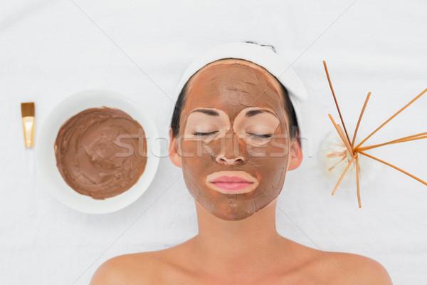 Smiling brunette getting a mud treatment facial Stock photo © wavebreak_media
