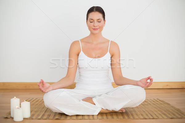 Sorridente morena sessão lótus pose olhando Foto stock © wavebreak_media