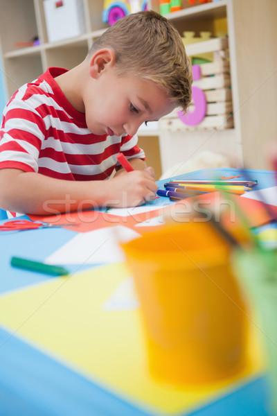 Cute little boy cutting paper shapes in classroom Stock photo © wavebreak_media