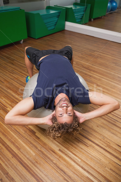 Man doing abdominal crunches on fitness ball in gym Stock photo © wavebreak_media