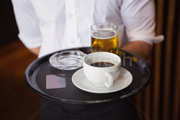 Waiter holding tray with coffee cup and pint of beer Stock photo © wavebreak_media