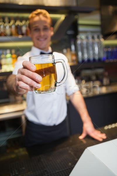 Glimlachend barman aanbieden pint bier Stockfoto © wavebreak_media