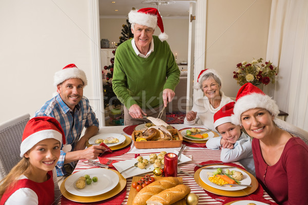 Grandfather in santa hat carving roast turkey at christmas dinne Stock photo © wavebreak_media